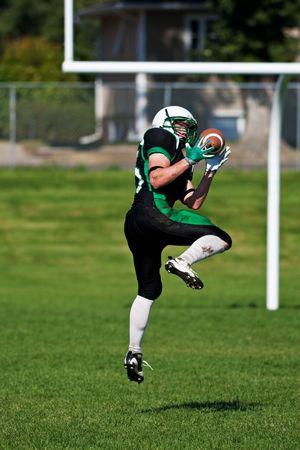 uniforme de futbol: Un jugador de f�tbol saltar fuera de la tierra, para atrapar la bola cerca de la porter�a.