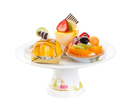 An assortment of Asian desserts, featuring (clockwise from top) Mousse Cake, Fruit Tart, and Mango Mousse.  Displayed on a pedestal cake plate and shot on white background. photo