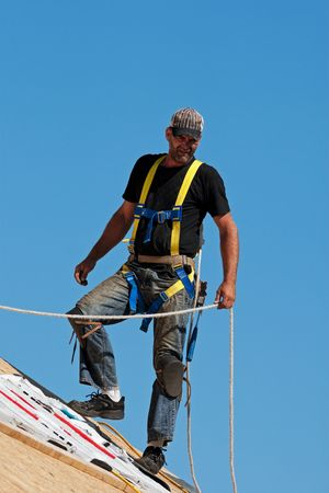shingle: Roofer with safety harness shingling a roof with a steep pitch.