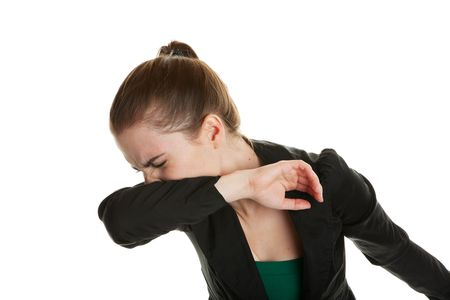 elbows: A young business woman, sneezing into her sleeve to prevent spreading germs.  Shot on white background.