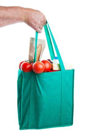 reusable: Una mano forte, detiene un sacchetto rispettoso pieno di generi alimentari.  Girato su sfondo bianco.