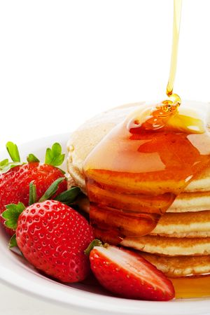 crepas: Jarabe de oro llovizna hacia abajo sobre caliente mantequilla panqueques con una guarnición de fresa.