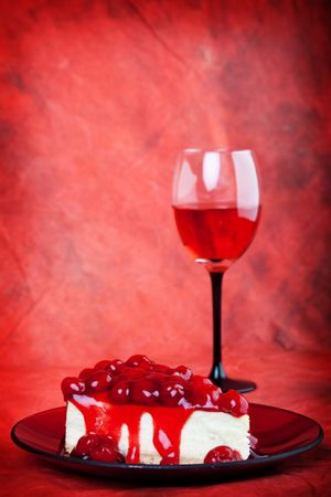 decadent: Decadent cherry cheesecake served on a candy apple red plate with red wine,on a red background.