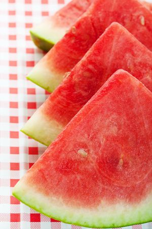 picnic cloth: Four watermelon wedges on a red, checkered picnic table cloth.  Shallow depth of field.