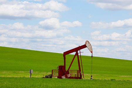 oil and gas industry: A pumpjack by a grassy hill. Alberta, Canada.