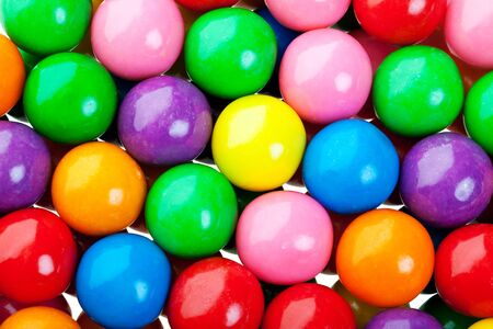 A colorful background of candy coated gumballs.