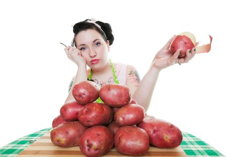 rockabilly: A young, rockabilly housewife depressed about the huge amount of potatoes she has to peel.  Shot on white background. Stock Photo