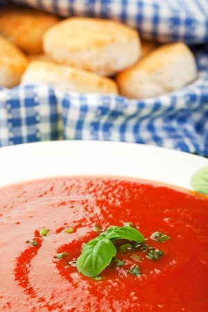 Tomato soup garnished with chives and a sprig of basil, with a basket of country fresh biscuits in the background.  Selective focus on basil.  Shallow dof.