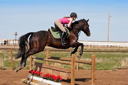 femme a cheval: Un jockey jeune, femelle sur son cheval sautant sur un obstacle.