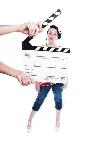 A clapper board being held up in front of a young actress dressed in rockabilly fashion.  Shot on white background.  Focus on clapper board. Imagens