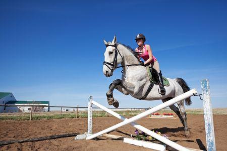 Un cavallo grigio bello, dappled con il pilota, saltando un ostacolo.