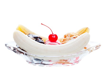 A scrumptious banana split, topped with caramel, strawberry, and chocolate, with a cherry garnish.  Shot on white background.
