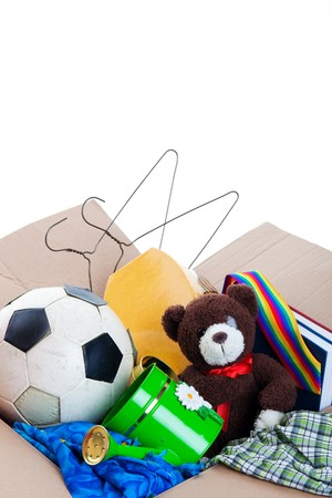 A box of unwanted stuff ready for a garage sale or to donate to a charitable organization.  Generic teddy bear.  Shot on white background. photo