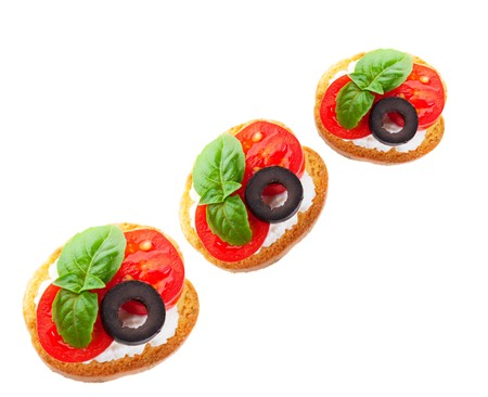 Juicy slices of baby tomato on a goat cheese covered baguette cracker, garnished with a slice of black olive and a fresh sprig of basil.  Shot on white background.