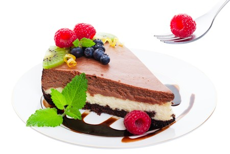New York Style, triple layer, chocolate cheesecake served on a chocolate drizzled plate and garnished with raspberries, blueberries, kiwi, and fresh sprigs of lemon balm.  Delicate citrus curls add a touch of elegance.  Shot on white background. photo