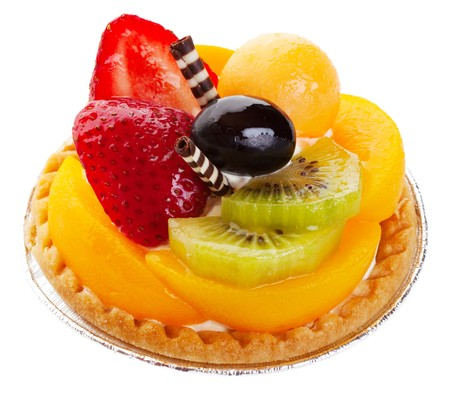 An Asian fruit tart stacked high with kiwi, peach, strawberries, melon balls, and a grape. Delicate rolls of striped white and dark chocolate garnish the center like mock chopsticks.  Shot on white background.