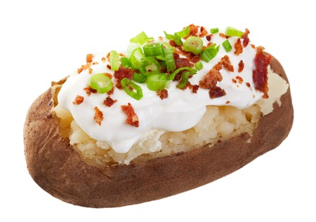 A baked potato loaded with sour cream, bacon bits, and chives.  Shot on white background. photo