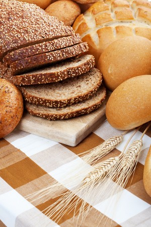 A variety of freshly baked breads along with three stocks of wheat.  Shallow depth of field. photo