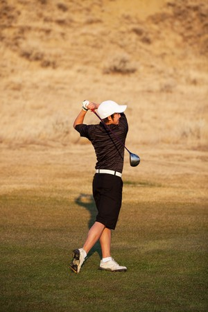 A skilled, mixed-race teenager playing golf.  Shot in early evening light. photo