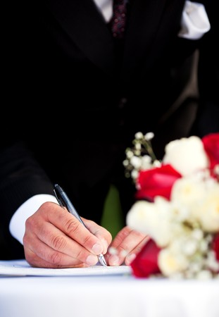 A groom signing his wedding license.  Focus on man's hand. Stock Photo