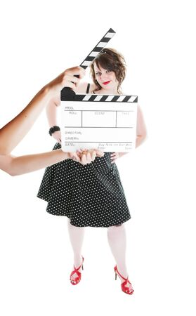 image size: A clapper board being held up in front of a young actress dressed in pinup fashion.  Shot on white background.  Focus on actress. Stock Photo