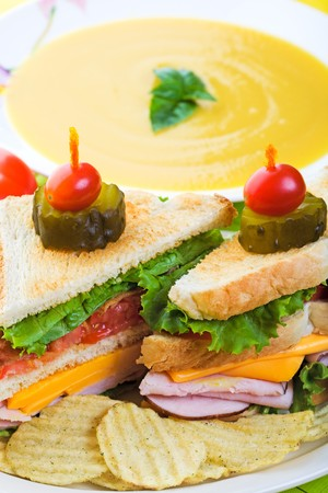 A delicious clubhouse sandwich, served with crunchy rippled potato chips and creamy butternut squash soup. photo