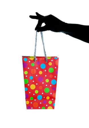A black gloved hand holding a Christmas gift bag with glitzy, silver tinsel handles.  Shot on white background. Stock Photo - 8196101
