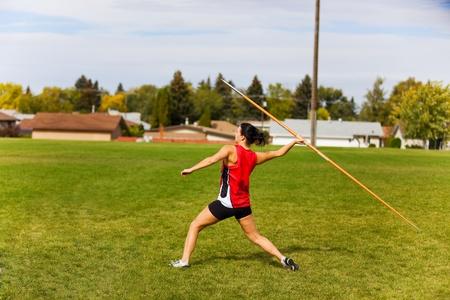 lanzamiento de jabalina: Un atleta j�venes, mujer, lanzando una jabalina en un evento de pista y campo. Foto de archivo