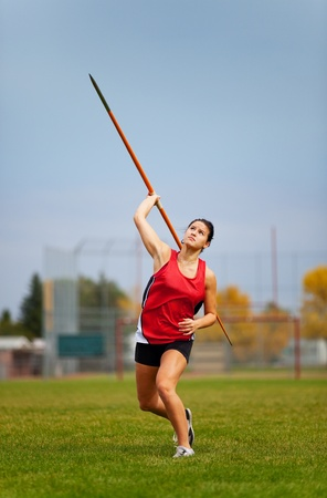 A young, female athlete throwing a javelin in a track and field event. photo