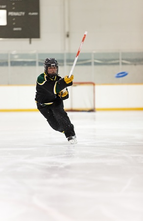 A young Ringette player throws the ring.