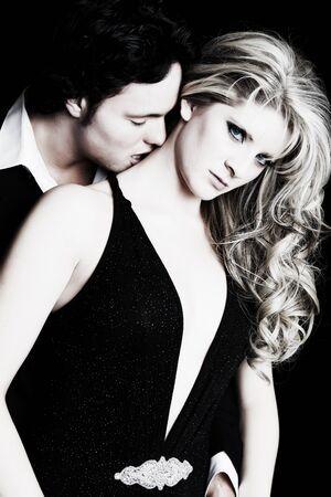 A young man seducing his beautiful girlfriend.  Formal wear fashion.