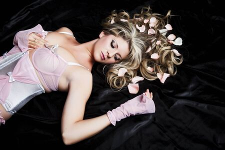A beautiful woman laying asleep with pink rose petals in her hair.