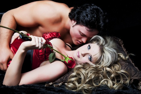 Romantic couple in lingerie with red rose on black background. Stock Photo - 9087201