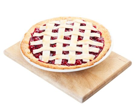 Delicious homemade cherry pie cooling on a wooden cutting board. Shot on white background. photo