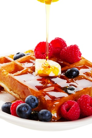 waffel: A stream of golden Canadian maple syrup adds the finishing touch to a delicious breakfast of belgian waffles with fresh raspberries and blueberries.  Shot on white background.