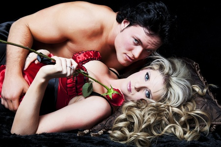 Romantic couple in lingerie with red rose on black background. Stock Photo