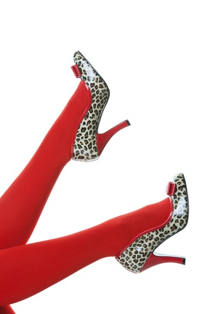 Beautiful red stockings, with red and animal print, rockabilly style high heels kicking up into the air.  Shot on white background.