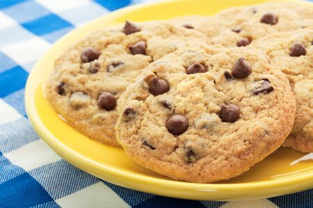 Homemade, chocolate chip cookies, like Mom used to make, served on a yellow plate.  Shallow depth of field. Stock Photo