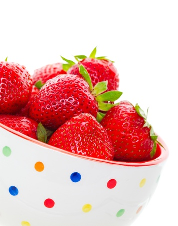 Ripe, juicy, freshly washed, strawberries heaped in a summer fun, polka-dot bowl.  Shot on white background. Stock Photo - 9677150