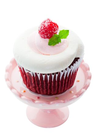 red velvet cupcake: Red Velvet cupcake with pink and white whipped cream cheese icing, and a sugared raspberry with a sprig of mint as garnish.