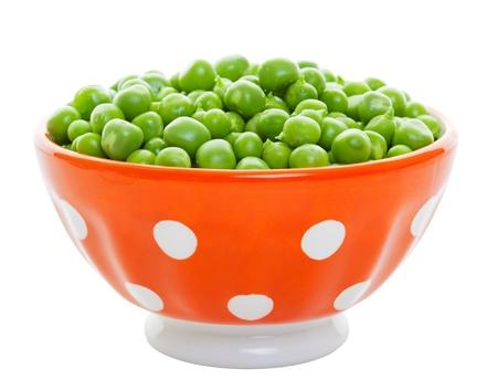 Raw, freshly shelled garden peas in an orange polkadot bowl.  Shot on white background. photo