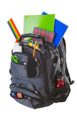 fournitures scolaires: Sac � dos rempli de fournitures scolaires.  Tourn� sur fond blanc. Banque d'images