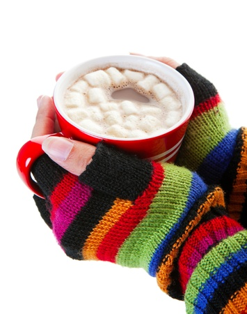 A mug of hot chocolate, complete with miniature marshmallows, warms cold hands on a cold day.  Shot on white background. photo