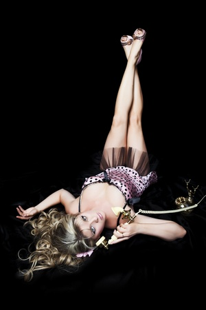 Pretty blond pinup girl in classic pose with telephone.  Black background.