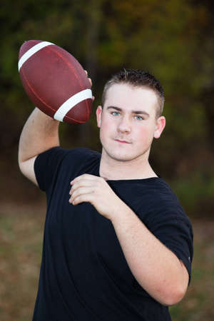 quarterback: Teenager throwing a football around in the park