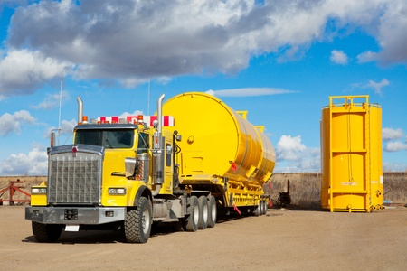 yacimiento petrolero: Un remolque de transporte de color amarillo recogiendo dos de nueva fabricación y recubiertos de 400 tanques de almacenamiento de campos petroleros BBL Foto de archivo