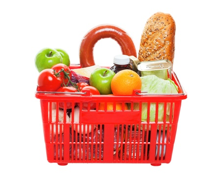 A grocery basket filled with fresh fruits, vegetables, sausage, bread, and canned goods   Shot on white background  photo