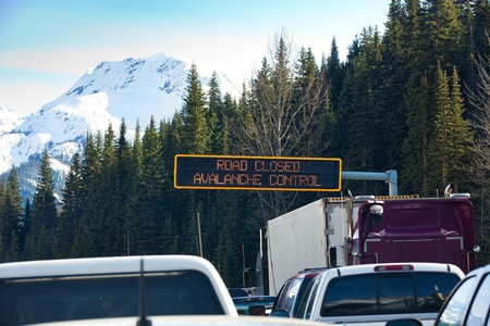 Travel through Roger's Pass in spring.  Traffic is stopped while avalanches are triggered with explosives and then cleaned from the road to ensure safe travel. Roger's Pass, British Columbia, Canada. Stock Photo - 13558673