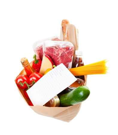 top angle view: Wide angle view of a grocery bag full of barbecue staples with a hand written grocery list on top.