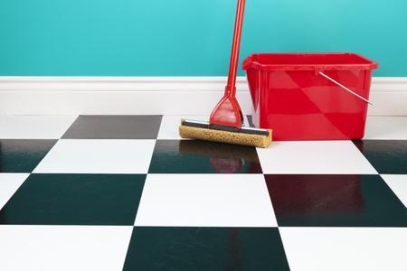 pulizia pavimenti: Un secchio rosso e scopa su un pavimento bianco e nero a scacchi contro un muro blu turchese Archivio Fotografico